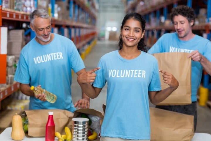 Portrait of volunteer pointing at t-shirt